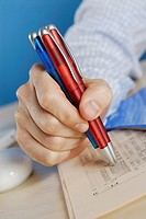 Close-up of a person's hand holding ballpoint pens on a sheet of paper