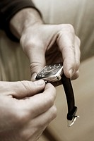 Close-up of a person's hand adjusting the time on a wristwatch