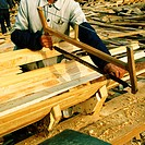 Mid section view of a carpenter sawing a plank, China