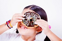 Close-up of a girl holding a donut in front of her eye