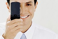 Portrait of a businessman covering his eye with a mobile phone