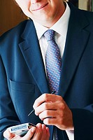 Close-up of a businessman using a personal data assistant