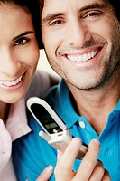 Portrait of a young man holding a mobile phone and smiling with a young woman