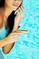 Close-up of a young woman holding a credit card and using a mobile phone