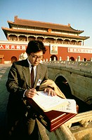 Businessman standing in front of a palace and writing with a pen on a sheet of paper, Tiananmen Gate Of Heavenly Peace, Tiananmen Square, Beijing, Chi...