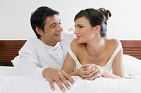 Close-up of a newlywed couple lying on the bed and smiling