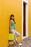 Portrait of a teenage girl leaning against the wall and holding shopping bags