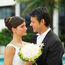 Close-up of a newlywed couple holding a bouquet of flowers and looking at each other