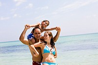 Mid adult man carrying his son on his shoulders with a young woman standing in front of him on the beach