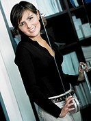 Portrait of a businesswoman holding the handle of a glass door