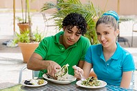 Close-up of a teenage girl and a young man eating salad and a wrap in a restaurant