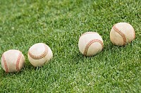Four baseballs on grass