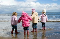 Group of 4, 4 year old girls standing on the seashore all in a row holding hands, dressed in winter clothing.