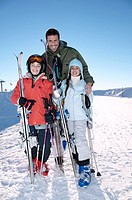 Portrait of a Father with His Two Children Standing on a Ski Slope