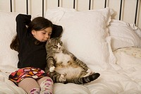 Girl 5-7 and cat lying on bed