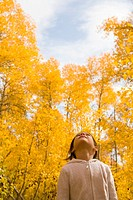 Girl 5-7 standing in forest, looking up, autumn, low angle view
