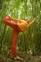 Woman practicing yoga in bamboo forest, side view, wide angle