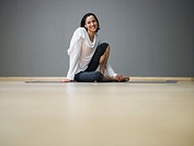Woman seated on yoga mat in exercise studio, smiling
