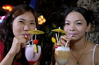 Young women drinking milkshakes, portrait, close-up