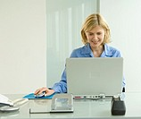 Young woman using laptop, smiling