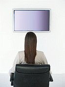 Young woman sitting in chair facing screen on wall, rear view