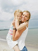 Mother holding daughter 6-8 standing on beach, smiling, portrait