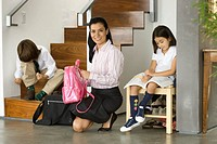 Mother helping children 6-10 get ready for school