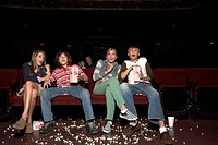 Four teenagers sitting in movie theatre auditorium