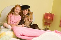 Two girls 7-10 and dog sitting on bed, portrait