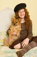 Girl 9-11 sitting on bed, holding dog, portrait