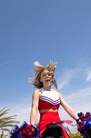Blurred Motion Shot of a Cheerleader Jumping and Cheering