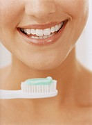 Close-up of Toothbrush, Toothpaste and a Womans Smiling Mouth