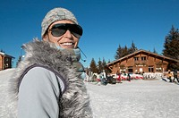 Portrait of a Woman in Skiwear and Sunglasses Standing by a Ski Chalet