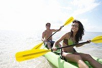 Young couple canoeing in bay, smiling