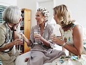 Three women with champagne flutes, sitting on bed, laughing