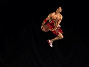 Male Basketball Player Jumping Mid Air Holding a Basketball