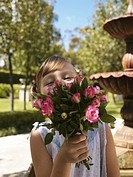 Girl 6-7 in bridesmaid´s dress holding up bouquet, portrait