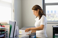 Young businesswoman sorting through paperwork in office