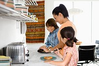 Mother preparing breakfast for children 6-10