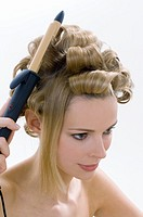 Young woman using curling tongs, close-up