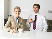 Colleagues with coffee cups, smiling, portrait