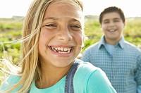 Children 10-12 in field, girl smiling