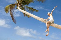 Fiji, young woman climbing palm tree, arm raised, low angle view