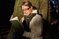 Woman leaning against tree reading book