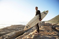 Man in wetsuit with surfboard on rocks