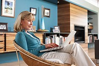 Mature woman using laptop at home, side view