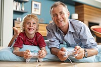 Father and son 5-7 playing computer game, smiling, low angle view