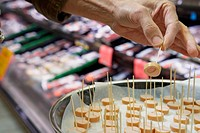 Woman trying food sample in supermarket