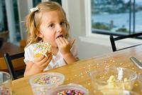 Girl 2-4 holding cake, licking fingers, portrait
