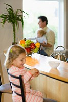 Father and two daughters sitting in dining area, differential focus